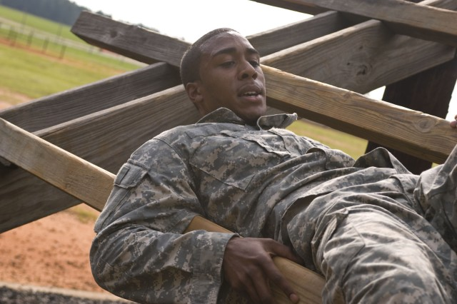 """FORT BRAGG, N.C. - Spc. Joel Hughes, a Soldier with the Headquarters and Headquarters Company of the 350th Civil Affairs Command in Pensacola, Fla., maintains his balance as maneuvers through the """"weaver"""" obstacle here on June 15, as part of the competition for this year's U.S. Army Civil Affairs and Psychological Operations (Airborne) Best Warrior selection. Hughes and 13 other Soldiers and noncommissioned officers from across the nation are competing to take home this year's Best Warrior of the Year Soldier, or NCO category. USACAPOC(A) is five percent of the U.S. Army Reserve Command's force and is responsible for approximately 20 percent of the Army Reserve deployments. The command is comprised of nearly 10,000 Soldiers in 67 units across 27 states and Puerto Rico."""