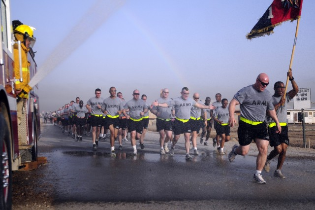 Col. Roger Cloutier, commander 1st Advise and Assist Brigade, 3rd Infantry Division, leads his brigade through a shower of water provided by Contingency Operating Station Falcon firemen, June 14, in Baghdad. The event was in recognition of the Army's 235th birthday.