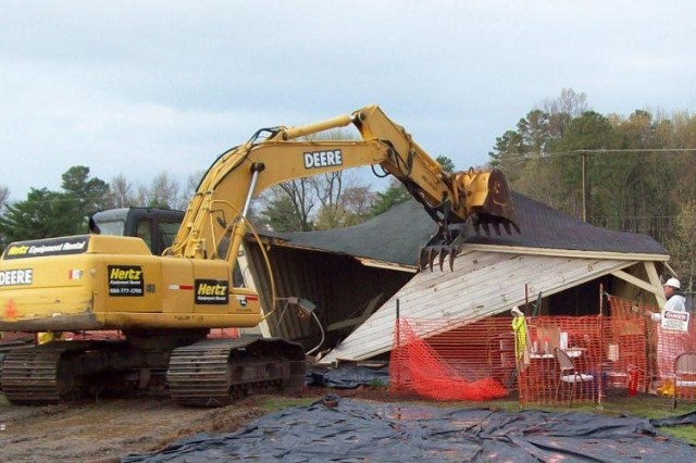 Environmental cleanup contractors demolish shed