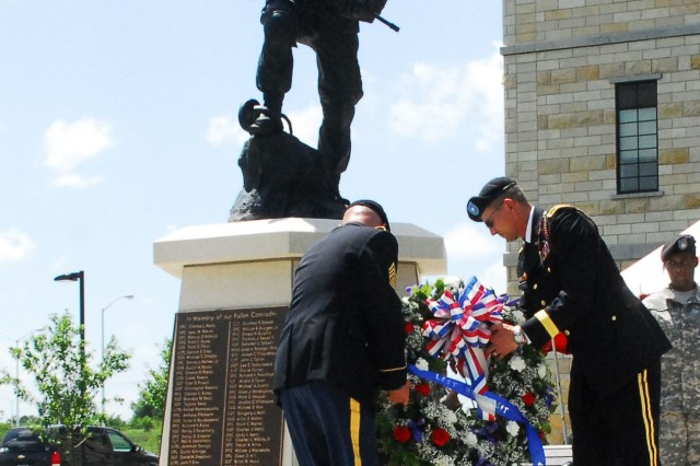 "Brig. Gen. David Petersen, 1st Infantry Division deputy commanding general-rear, and Command Sgt. Maj. ""Buddy"" Wallace, 1st Infantry Division command sergeant major-rear, place a wreath in front of the Fallen Soldier Memorial during the Victory Park Ceremony at Fort Riley June 17."