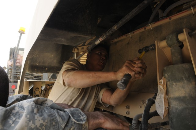 Sergeant Orlando Boneshirt, a light-wheeled vehicle mechanic for Headquarters and Headquarters Company, Division Special Troops Battalion, 3rd Infantry Division, hammers a bolt through the mounting bracket for the shocks on a mine-resistant, ambush protected (MRAP) vehicle. As the motor pool's unscheduled services chief, Sgt. Boneshirt oversees many on-the-spot repairs for vehicles within the battalion.(U.S. Army photo by Sgt. Johnathon Jobson, TF Marne Public Affairs.)