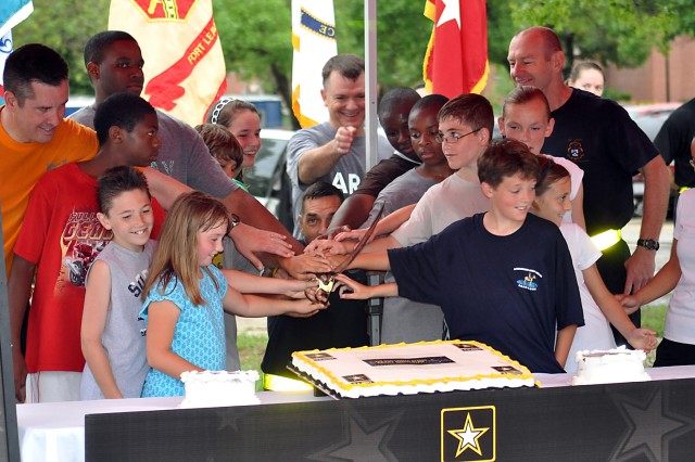 """Combined Arms Center Deputy to the Commanding General Dale Ormond, CAC Command Sgt. Maj. Philip Johndrow, CAC Training Deputy Commanding General Col. Paul Funk II and Command and General Staff College Deputy Commandant Maj. Gen. Edward Cardon are joined by young Soldiers and family members for a cake cutting during the 235th Army birthday celebration June 14 in the Bell Hall parking lot, Fort Leavenworth, Kan. The celebration also included a fun run and Soldiers reading essays they wrote titled """"Why I am proud to be an American Soldier."""""""