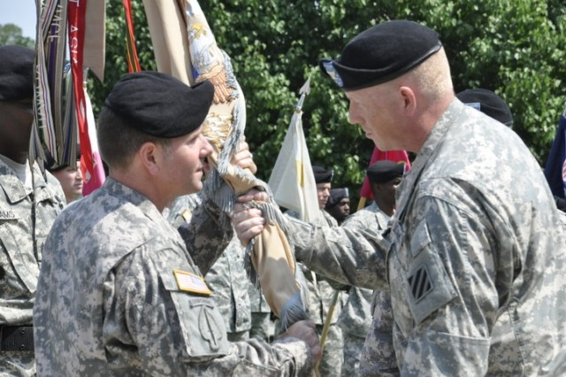 Colonel Stuart J. McRae, 3rd ID rear detachment commander, passes the colors of the 260th Quartermaster Battalion to Lt. Col. James L. Brown, incoming commander, during the 260th Quartermaster Bn. change of command at Fort Stewart's Marne Garden, June 10.