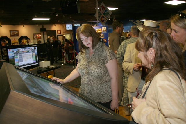 FORT CARSON, Colo.--- Cindy McLaughlin, wife of Garrison Commander Col. Robert F. McLaughlin, checks out the Warrior Family Community Partnership touch-screen information board at Alternate Escapes during a WFCP social event.