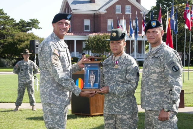 Staff Sgt. Melissa Solomon (108th Reserve Division) receives the 2010 Drill Sergeant of the Year award from Lt. Gen. Mark P. Hertling, deputy commanding general of Initial Military Training, and Command Sgt. Maj. John Calpena, the senior enlisted advisor for Initial Military Training, during a ceremony at Fort Monroe, Va.