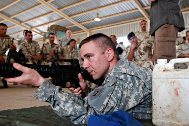 Sgt. Kevin Averre, a Soldier with the Combat Aviation Brigade, 1st Infantry Division., demonstrates a firing position to Iraqi Army soldiers. Averre and several other Soldiers from the conducted weapons training with Iraqi troops on Camp Taji, Iraq, June 15, assisting the Iraqi Army's transition from the AK-47 to the M-16.