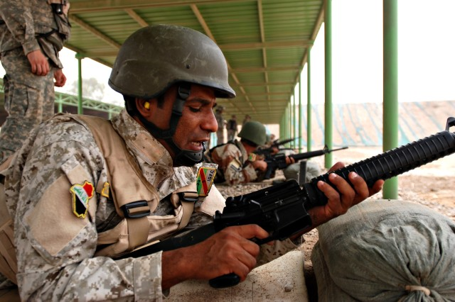 An Iraqi Army soldier examines his M-16 rifle during weapons training with U.S. Soldiers on Camp Taji, Iraq, June 15. The Iraqi Army is currently replacing their arsenal of older AK-47s with the M-16.