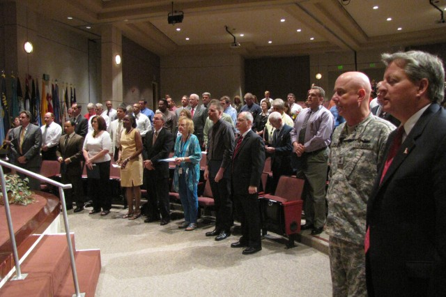 Team Redstone employees stand to be recognized during the Deployed Workforce Recognition Ceremony in Bob Jones Auditorium. The employees have all voluntarily deployed from Redstone Arsenal to support Soldiers.