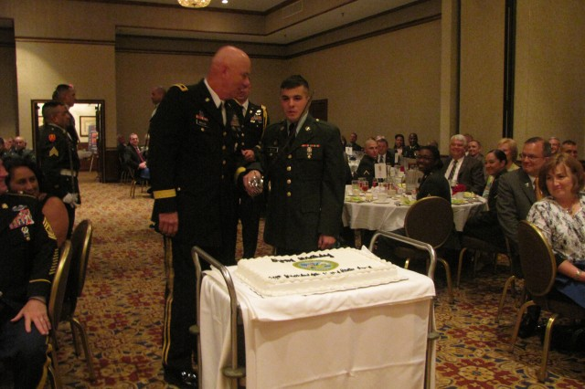 Pvt. Jake Betts joins Redstone Arsenal's Maj. Gen. Jim Myles for the cutting of the Army birthday cake with a saber during the 235th Army Birthday Dinner hosted by the Redstone-Huntsville Chapter of the Association of the U.S. Army.