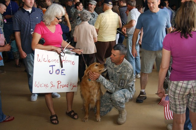 LATHAM, NY-- 206th Military Police Company mbmer Staff Sgt. Joe Lyndon is greeted by the family dog upon his return to the company's home station at New York State Division of Military and Naval Affairs Headquarters here on Friday, June 18. More than 70 Soldiers from the Albany, NY-area return here on Friday while other members of the 160-Soldier unit had home comings in the Hudson Valley, Utica, Auburn, Rochester and Buffalo.