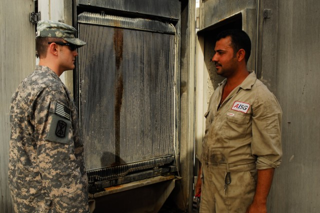 Spc. Joshua Upman (left), Headquarters and Headquarters Battery, 17th Fires Brigade, supply clerk and native of Nashville, Tenn., discusses the status of an overheated generator on Camp Brady Lines at Contingency Operating Base Basra in southern Iraq.
