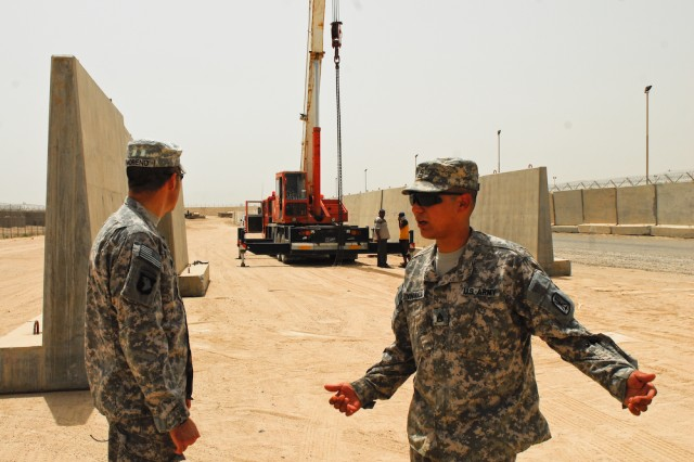 Staff Sgt. Mark Vindiola (right), noncommissioned officer-in-charge of the 606th Forward Support Company's Facilities Engineer Team and native of Hacienda Heights, Calif., explains the Camp Bucca layout change to his replacement Sgt. Alfredo Moreno (left), NCOIC of the Company A,, 3rd Battalion, 141st Infantry Regiment Facilities Engineer Team and native of Brownville, Texas.