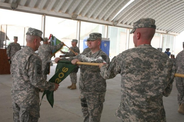 206th Military Police Company commander, Capt. Kevin Manion (center) and 1st Sgt. Joseph Martel, 206th MP Company first sergeant, furl their company's guidon during the 203rd MP Battalion and 206th MP Company End of Nission Ceremony at Contingency Operating Base Basra June 6.