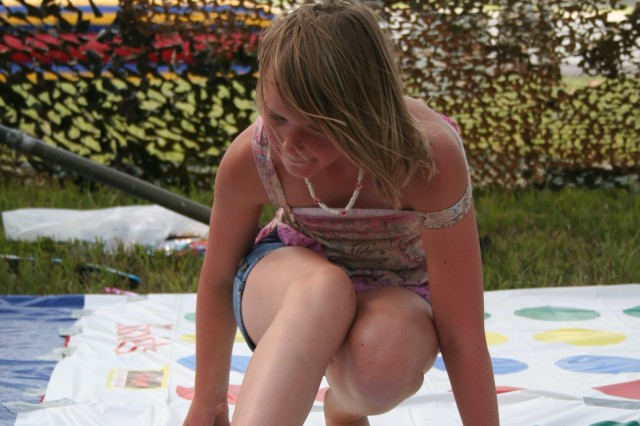 Jessica Bassett-Walker, 11, tries her luck at the game Twister during the Victory Week festival and concert June 18 on Marshall Army Airfield.