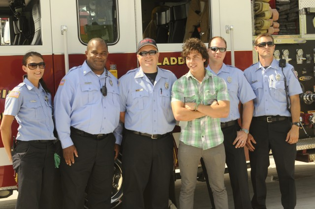 Cameron Quiseng, a member of the band, Allstar Weekend, poses for a picture with members of the Fort Riley Fire Department during the Victory Week festival and concert June 18 on Marshall Army Airfield, Fort Riley.