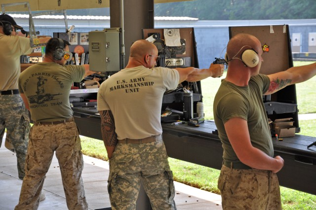 FORT BENNING, Ga. -- Staff Sgt. Robert Park (middle), U.S. Army Marksmanship Unit, fires downrange June 17 during the 51st Interservice Pistol Championships. Park won the overall individual championship and was a member of the U.S. Army Blue team, the overall team champions for 2010. (Photo by Michael Molinaro, USAMU PAO)