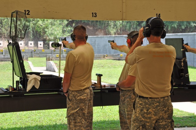 FORT BENNING, Ga. -- Army Reservists Master Sgt. Robert Mango (left) and Sgt. 1st Class Keith Sanderson (right), fire during the service pistol team match as Lt. Col. Alan Toler looks on June 17 at Phillips Range, site of the 51st Interservice Pistol Championships. All three were members of U.S. Army Reserve Team Black, which won two team matches during the week and finished in third place overall. (Photo by Michael Molinaro, USAMU PAO)