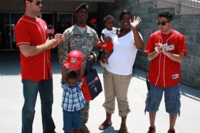 Staff Sgt. Kelvin Ladner, 1st Army Division East, his wife Stephanie, and sons Kelvin Jr. and Jayden receive a baseball prize pack from the Washington Nationals as they are recognized during the Fathers Day Military Appreciation game June 20, 2010.