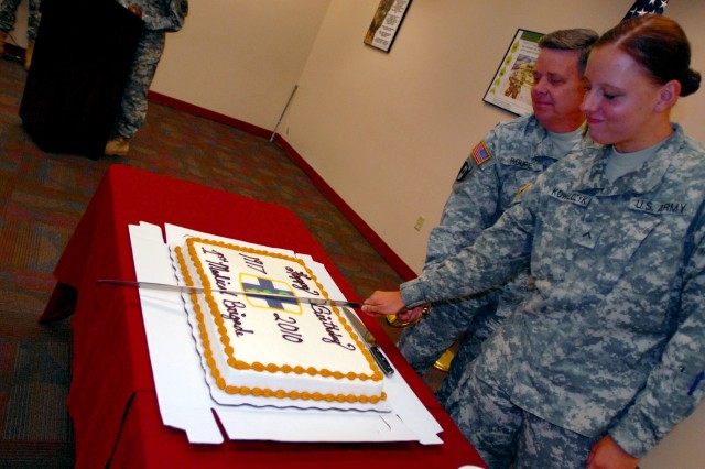 Pvt. Anne Lauren Kowalcyzk, 28th Veterinarian Medical Detachment, 1st Medical Brigade, and Lt. Col. Lee Roupe, the Silver Knight Brigade provisional commander, sliced the unit's birthday cake June 4 at Fort Hood, Texas. Kowalcyzk is the unit's youngest Soldier. (U.S. Army photo by Pfc. Sean McGuire)