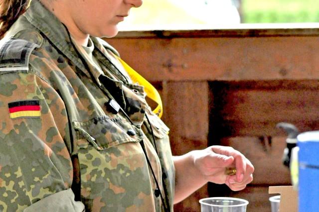 German Stabsunteroffizier (Sgt.) Tamara GAfAPtzl, HeeresfAfA1/4hrungskommando, fills the ammunition containers at the team competion June 11.