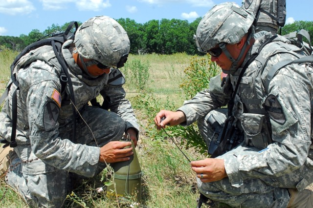 FORT HOOD, Texas- Spc. Joshua Smith (left), a Fort Worth, Texas native, and 2nd Lt. Stephen Karr, both with Company C, 2nd Special Troops Battalion, 2nd Brigade Combat Team, 1st Cavalry Division, rig an explosive during field training on Fort Hood, Texas, June 16.