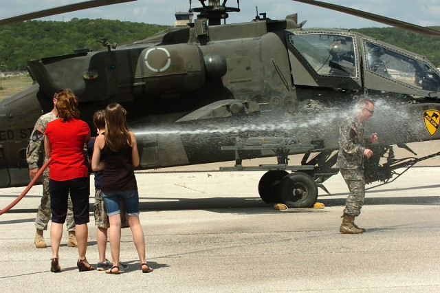 FORT HOOD, Texas-Following his final flight, after 25 years in an AH-64D Apache attack helicopter, Col. Douglas Gabram, from Cleveland, Ohio, commander, 1st Air Cavalry Brigade, 1st Cavalry Division, is hosed down by his wife Lori, son Connor and daughter Sarah, at Robert Gray Army Airfield, June 15. The hosing indicates the end of an aviator's career flying aircraft.
