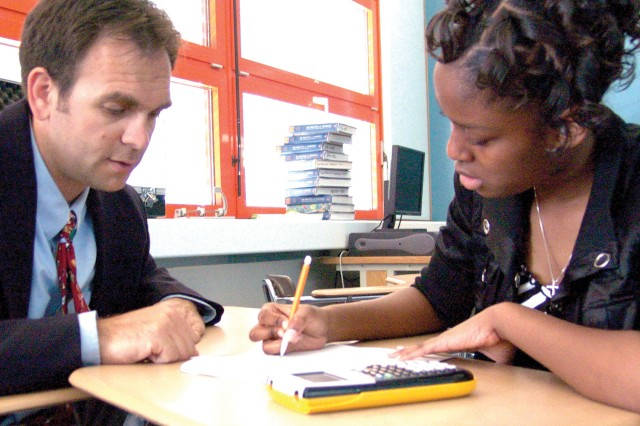 Baumholder Middle High School math teacher Michael Kelly works with Natasha Jenkins, an Algebra student, on some school work.
