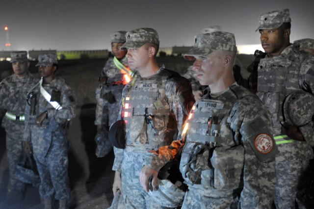 Staff Sgt. Jared Meier and Spc. Stephen Levins, both representing the 1st Theater Sustainment Command, ready themselves for the Urban Land Navigation course portion of Third Army's Soldier/NCO of The Year competition at Camp Buerhing, Kuwait, June 15.  The course was designed to emulate situations in Iraq and Afghanistan where Soldiers routinely navigate through cities and towns. (Photo by Sgt. Daniel Lucas, 203rd Public Affairs Detachment)