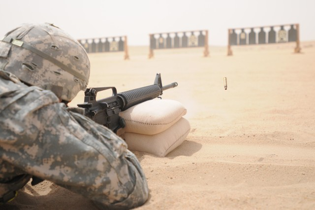 Spc. Stehpen Levins, competing for the 1st Theater Sustainment Command, qualifies with an M-16 at a firing range near Camp Buerhing, Kuwait, Jun 15.  The competition pitted Soldiers against the heat and the clock to qualify and prove their Basic Marksmanship skills. (Photo by Sgt. Daniel Lucas, 203rd Public Affairs Detachment.)