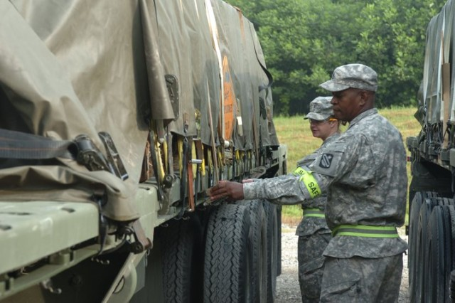 Sgt. 1st Class Irvin Ely, 310th CSSB safety NCO (foreground) and Chief Warrant Officer Melanie Shields, 310th CSSB safety officer, perform final safety checks on a trailer. The loads must be secured to ensure there is no shifting during transportation due to the nature of the cargo.