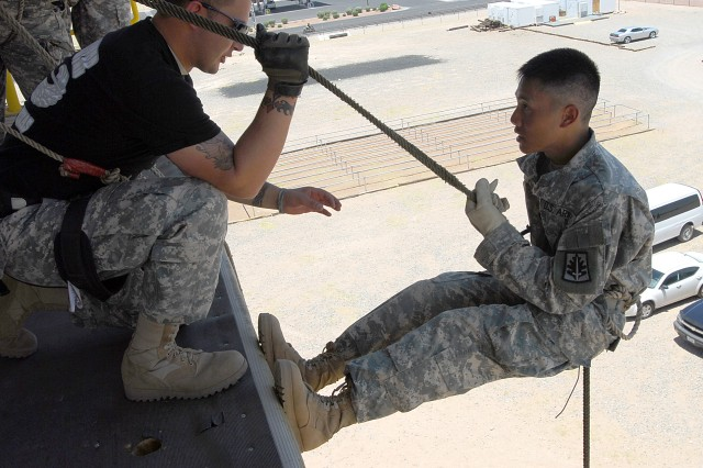 Air Assault Soldier of Headquarters and Headquarters Company, BSB, 5th Brigade Combat Team, 1st Armored Division, Spc. Caleb Zavala, coaches Spc. Ruifu Zhao as he rappels a tower at Fort Bliss, Texas, June 18, 2010. Zhao, a 310th MP Battalion Soldier, is participating in the Army Reserve 200th Military Police Command's Operation Guardian Justice, a combined Annual Training and Mobilization Training exercise at nearby Camp McGregor, N.M., involving about 1,000 Soldiers from across the country and Puerto Rico.