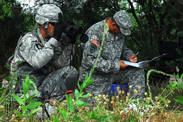 FORT HOOD, Texas- Spc. Don Pierce (left), an infantryman with 1st Battalion, 8th Cavalry Regiment, 2nd Brigade Combat Team, 1st Cavalry Division, checks the distance of his target before simulating calling for fire during Expert Infantryman Badge testing, June 15.