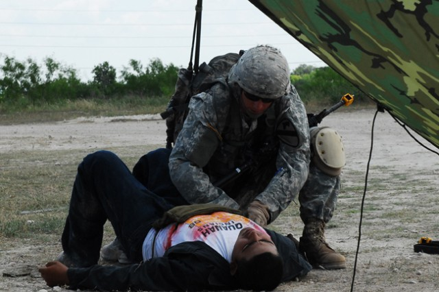 FORT HOOD, Texas- Sgt. Jake Berger, an infantryman with 1st Battalion, 12th Cavalry Regiment, 3rd Brigade Combat Team, 1st Cavalry Division, demonstrates the proper technique of treating a chest wound on a casualty during Expert Infantryman Badge testing, June 15
