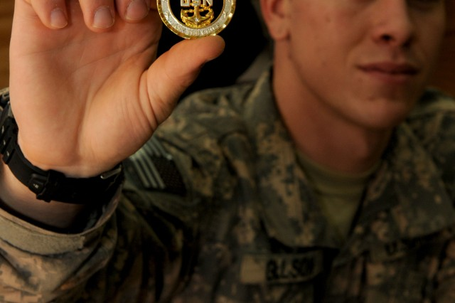 Corporal Eric Gillson, a chaplain assistant, currently assigned under 3rd Infantry Division, holds up one of his favorite coins he has earned during his deployment at Contingency Operating Base Speicher, Tikrit, Iraq.