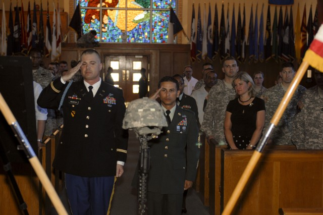 FORT HOOD, Texas-Capt. David McCarthy (left) and 1st Sgt. Jorge Velez, the command team of Headquarters and Headquarters Troop, 3rd Brigade Combat Team, 1st Cavalry Division, render honors to Spc. Robert Rose, the unit's chemical, biological, radiological, nuclear and explosives specialist at his memorial service, June 22, at Fort Hood's Memorial Chapel.