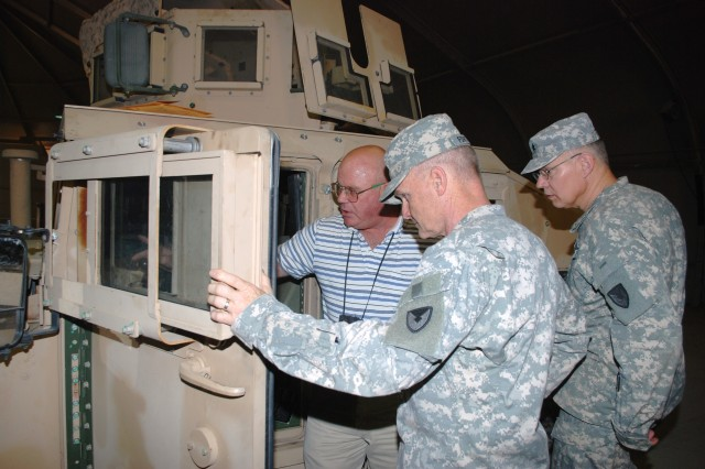 John A. Bonham, logistics management specialist with the Support Operations Office of the 1st Battalion, 402nd Army Field Support Brigade, shows an M1151 vehicle fitted with a Fragmentation Kit 7 to Maj. Gen Yves Fontaine (center), commanding general, Army Sustainment Command, Rock Island Arsenal, Ill., and Brig. Gen. Steven Feldmann, deputy commanding general for operations, ASC, during their visit to Joint Base Balad, Iraq, June 7. Bonham, is the 402nd AFSB Maintenance site lead and Add on Armor/Frag 7 project officer. He also oversees the brigade\'s Repair and Return Program for the Tactical Wheeled Vehicle fleet and National Maintenance Program for Tire and Wheel Assemblies. He is deployed from Warren, Mich., where he is a logistical maintenance management specialist with TACOM-LCMC.