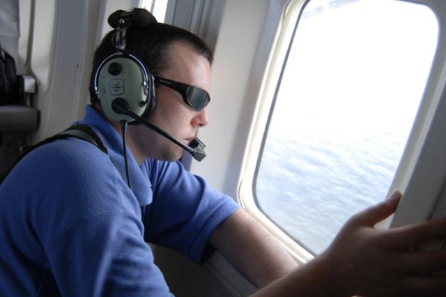 On board a Florida National Guard C-23 Sherpa airplane, Byran Schoonard, a research associate with the Florida Fish and Wildlife Conservation Commission, scans the waters off of Destin, Fla., for signs of oil from the Deepwater Horizon oil spill, June, 22, 2010. Florida Army National Guard aviators have been working closely with Florida Fish and Wildlife by taking its specialists up for daily observation flights over the Gulf of Mexico.