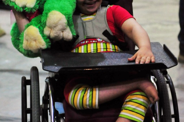 BAGHDAD - An Iraqi girl happily plays with a stuffed animal given to her by Soldiers of 1st Armored Division at Camp Liberty June 21. The girl is sitting in a pediatric wheelchair given to her free of charge during the Wheelchairs for Iraqi Kids event in which volunteers from all military branches participated. (U.S. Army photo by Sgt. Teri Hansen, 366th MPAD, USD-C)