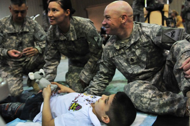 """BAGHDAD - Command Sgt. Maj. Sal Katz, the senior noncommissioned officer of Division Special Troops Battalion, 1st Armored Division, is introduced to Abdallah, an Iraqi boy who received a pediatric wheelchair at Camp Liberty June 21. Katz, a Los Angeles native, played with the boy throughout the afternoon. """"Abdallah touched my heart,"""" said Katz. (U.S. Army photo by Sgt. Teri Hansen, 366th MPAD, USD-C)"""
