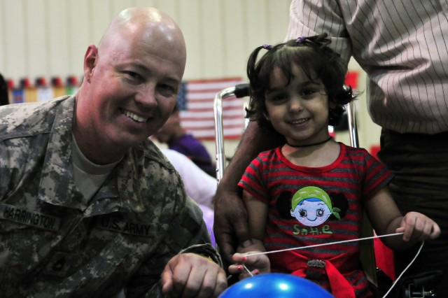 BAGHDAD - Sgt. 1st Class William Harrington, an imagery analyst with Company A, Division Special Troops Battalion, 1st Armored Division, poses for a picture with an Iraqi girl at Camp Liberty June 21. Harrington, a Memphis, Tenn., native, adjusted a pediatric wheelchair to fit the child, who can't walk, during a Wheelchairs for Iraqi Kids event in which approximately 40 wheelchairs were given to families free of charge. (U.S. Army photo by Sgt. Teri Hansen, 366th MPAD, USD-C)