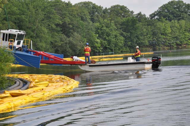 A barge is lowered in to Lake Cochituate to help with the clean up and dredging of the lake. The project is expected to last two months this summer.