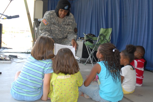 Col. Lillian Dixon, shown here reading to a group of school children, will relinquish command to Col. James Love in a ceremony Friday.