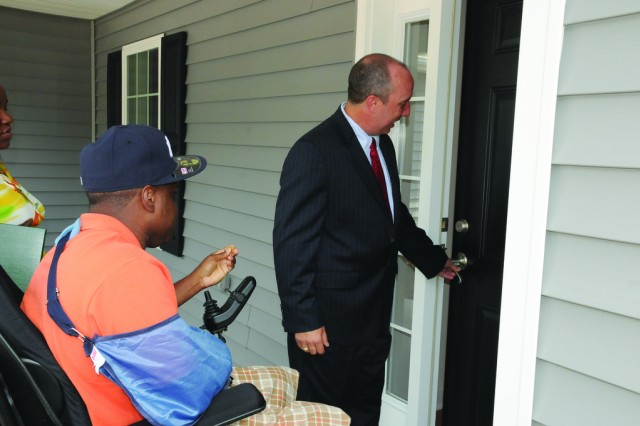 John Gonsalves, Homes For Our Troops president and founder, opens the door to the new home for Staff Sgt. Dwayne Cole and his wife, Shontel, after the key ceremony June 19.