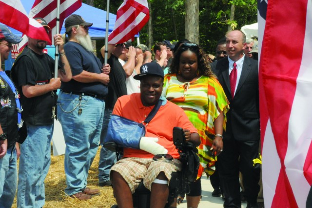 Staff Sgt. Dwayne Cole and his wife Shontel travel on the front walk to their new home as members of the Patriot Guard show their support after the key ceremony by Homes For Our Troops, June 19.