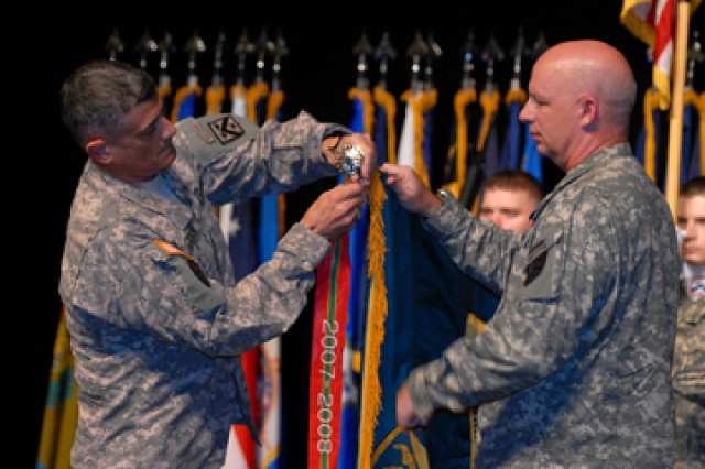 Combined Arms Center and Fort Leavenworth Commander Lt. Gen. Robert Caslen Jr., with Battle Command Training Program Commander Col. Mark McKnight, attaches the Army Superior Unit Award streamer to BCTP's recently unfurled colors June 22 at the Lewis and Clark Center's Eisenhower Auditorium.