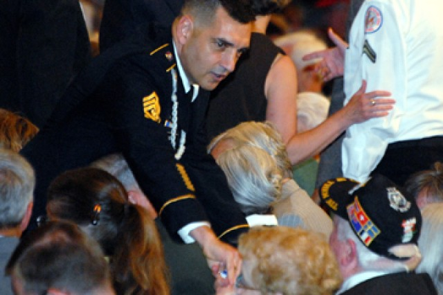 Combined Arms Center Command Sgt. Maj. Philip Johndrow greets and gives a coin to a veteran before the Korean War Veterans Appreciation ceremony June 21 at the Community of Christ Auditorium in Independence, Mo.