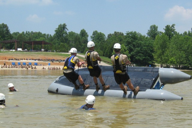 To right the raft, three cadets put their weight all on one side.