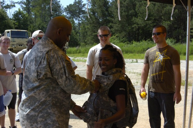 Future Soldier Kanitra Johnson, a sophomore at Wesleyan College, tries on Maj. Fidel Perez\'s body armor at an annual U.S. Army Reserve Command training event with the 1-347th Combat Service Support Battalion at Fort Gillem, Ga., June 17.