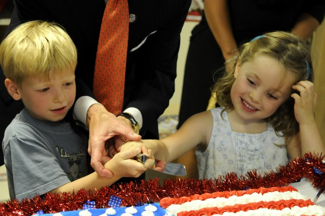 With the aid of 5-year-olds Liam O'Grady Walsh (left) and Janey Volkwein, Secretary of the Army John McHugh helps cut a cake celebrating the Army's 235th birthday at the Cody Child Development Center on Joint Base Myer-Henderson Hall June 17.