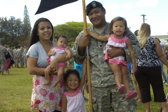 An Soldier serving with Company C., 1st Battalion, 21st Infantry Regiment, 2nd Brigade Combat Team, 25th Infantry Division gathers with his family following the brigade's deployment ceremony held at Sills Field on Schofield Barracks, Hawaii, June 24. The brigade will be deployed to the northern Iraq region for 12-months as they serve in an advise and assist role alongside Iraqi military and government leaders. (U.S. Army photo by Spc. Jesus J. Aranda, 25th Infantry Division Public Affairs Office)